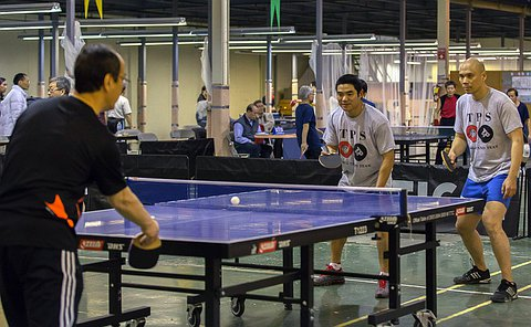 A man on the left serves a ball at a table tennis game as two other men across the table anticipate the path of the ball