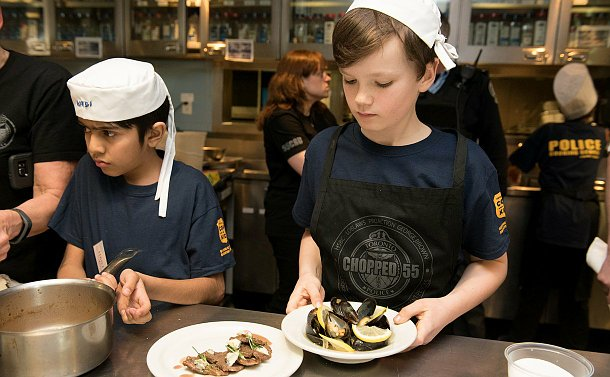 A young boy waring a chef's hat looking down at a plate of mussels