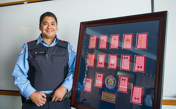 Man standing in-front of a display with pink epaulettes