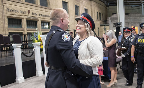 A man in TPS uniform holding a woman wearing a TPS hat