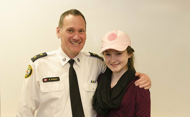A man in TPS uniform and a girl wearing a TPS baseball cap