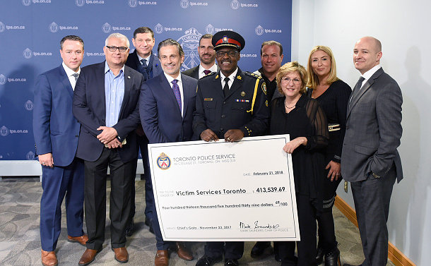 Group of men and women, in front of a large cardboard cheque written to Victim Services Toronto in the value of $413,539.69