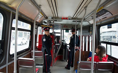 Two officers standing at the front of a streetcar, their heads are turned looking back.