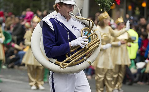 A marching band member playing a horn instrument adorned with a wreath