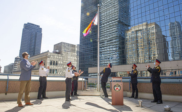 A group of poeple, some in TPS uniform raising a rainbow flag
