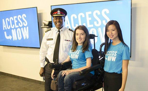 A man in TPS uniform beside two women