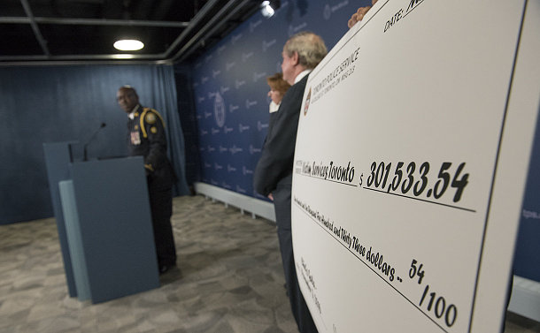 A large cheque with a man in TPS uniform at the podium
