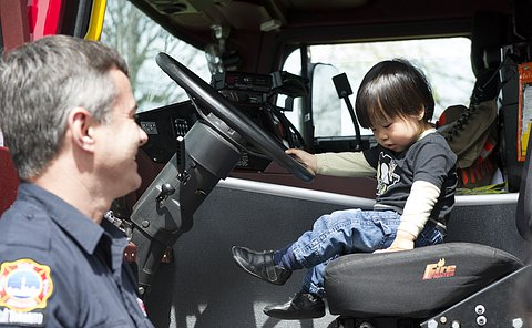 A small boy in the driver's seat of a fire truck as a firefighter looks on