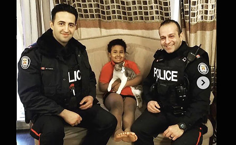 Two men in TPS uniform with a boy and a cat on a couch