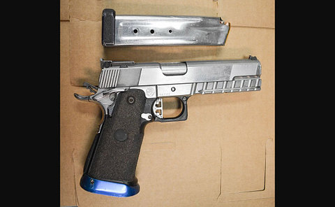 A silver handgun and clip on cardboard