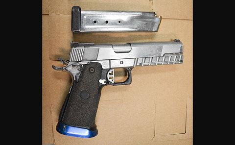 A silver handgun and clip on cardboard