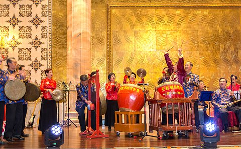 A group of people drumming on a stage