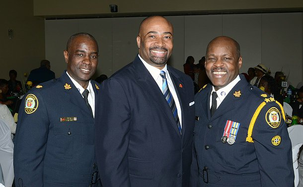Two men in Toronto police uniform with another man standing in a row