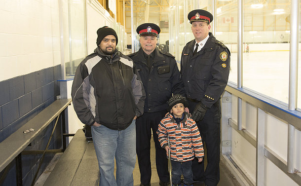 A man and a boy with two men in TPS uniform on a hockey bench