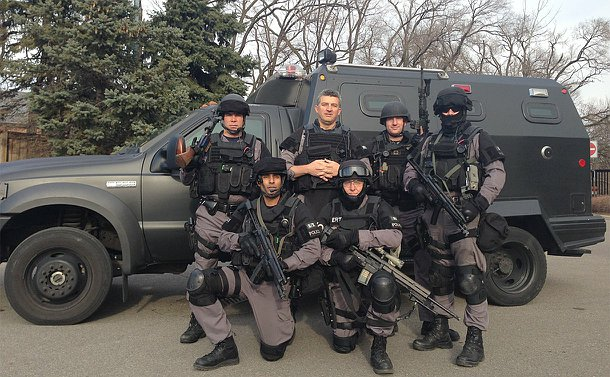 A group of officers in TPS tactical gear in front of a large tactical truck