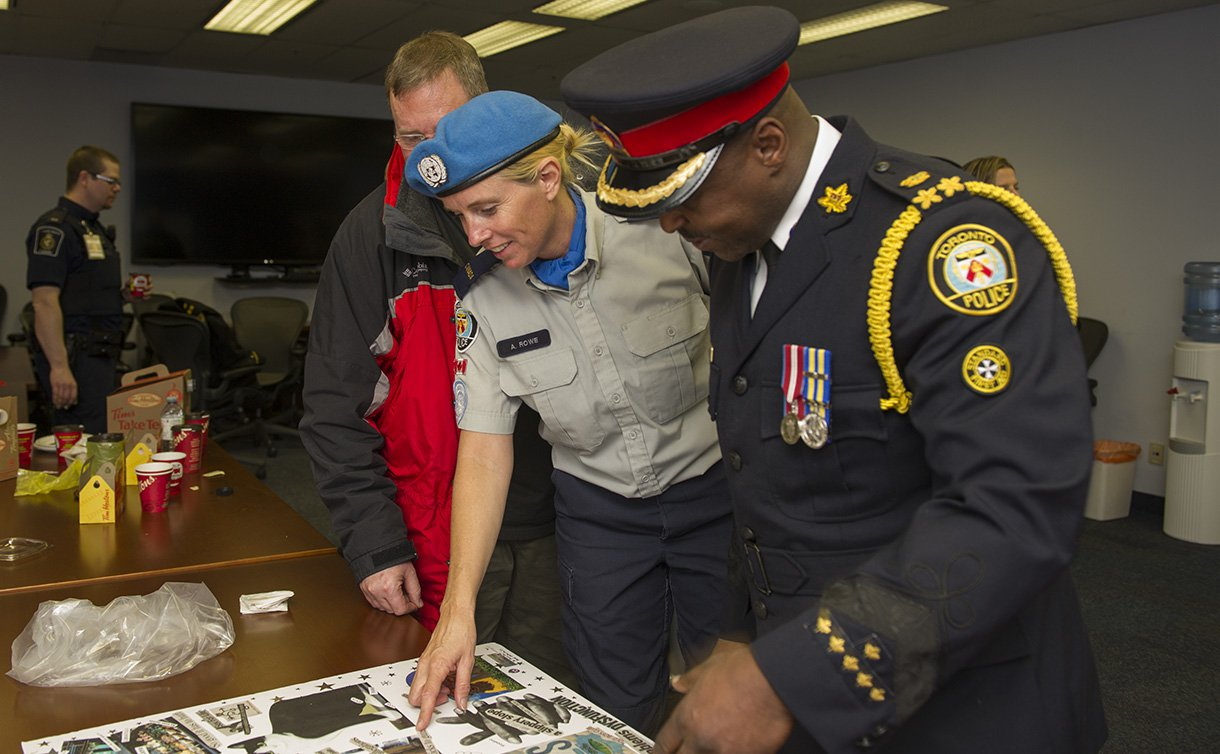 An officer in UN peacekeepers uniform standing next to an officer in dress uniform looking at a picture on a table