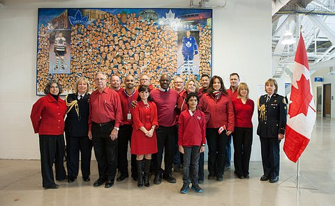 A group of people standing by a Canadian flag wearing red clothing except for two women wearing TPS uniforms
