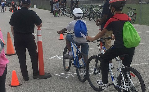 A man in TPS uniform stands beside children on bicycles in a parking lot with many orange cones