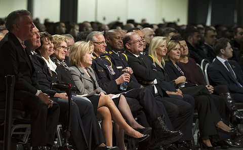 A front row of a crowd of people in business wear or uniforms smile