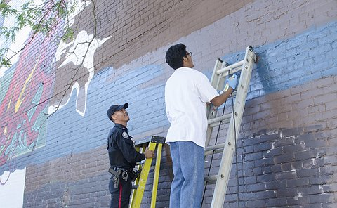 A man in TPS uniform on a ladder beside a teenage boy on a ladder with a can of spray paint