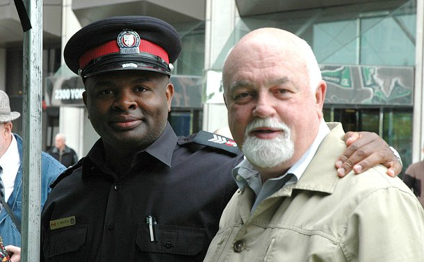 One man in Toronto police uniform with his arm around another man
