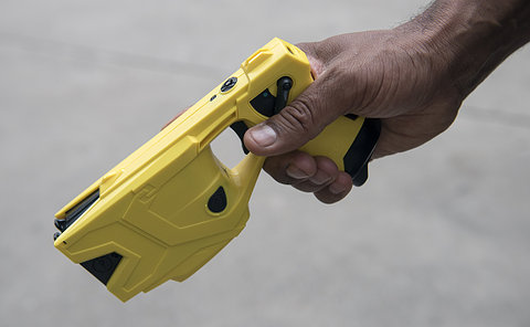 A hand holding a yellow plastic weapon