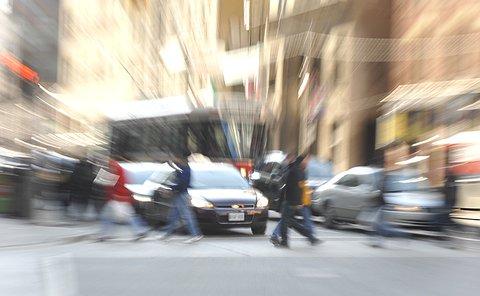 Pedestrians cross at an intersection as cars wait