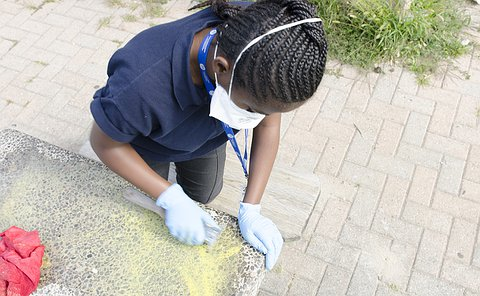 A teenage girl leans over a concrete table scrubbing it