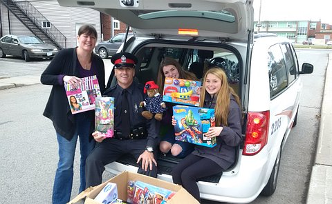 A woman and two girls holding toys with a man in TPS uniform sitting in the trunk of a TPS minivan