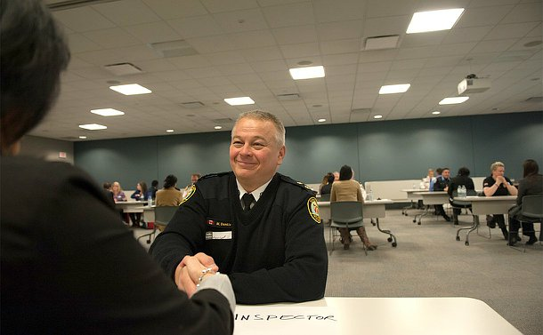 A man in TPS uniform sitting at a table shakes another hand