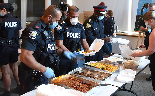 A group of police officers packaging food in takeout containers