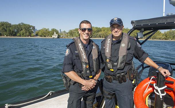 Two men in TPS uniform on a boat