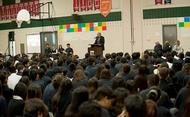 A man at a podium in a gym auditorium with students sitting on the ground watching him speak. All students  are wearing uniforms.