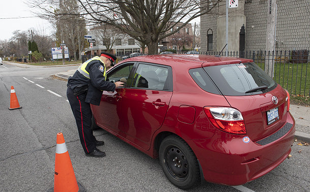 A man in TPS uniform leaning down at a car