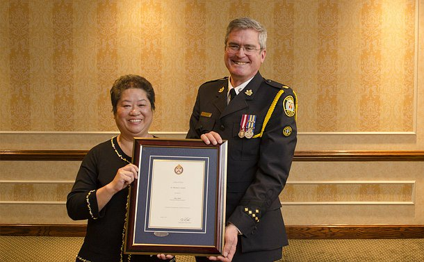 A woman stands next to a man in TPS uniform, both holding a framed certificate