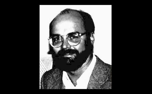 Black and white close-up photo of a man with a beard wearing glasses