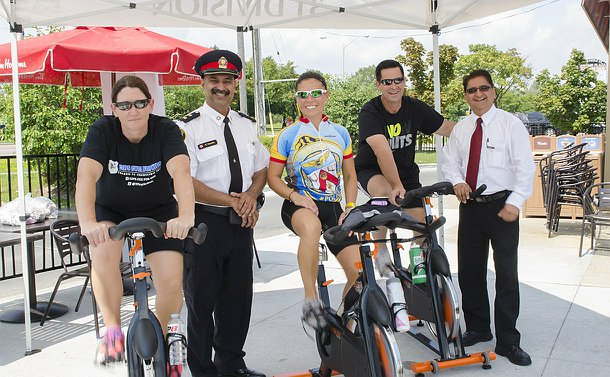 Two women and one man on stationary bikes while two other men, one in TPS uniform, stand between them