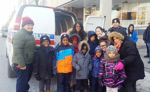 A group of children and adults by a TPS van