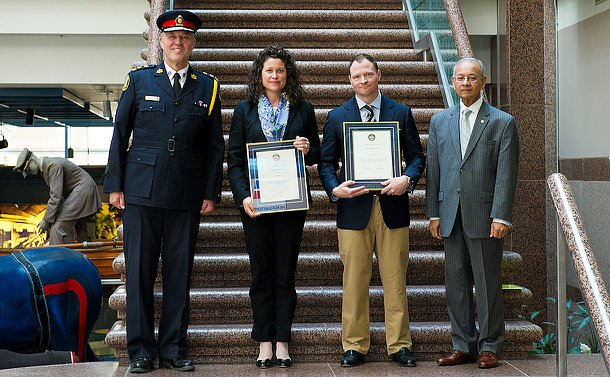 A man and a woman holding plaques with the chair of the police board in suit to their right and the chief in uniform to their left.