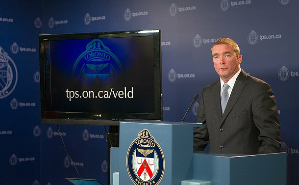 A man in front of a podium with a Toronto police logo with a tv screen next to him which is displaying a url.