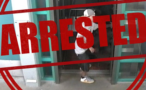 An image of a man by an elevator from a surveillance camera with the word arrested over top