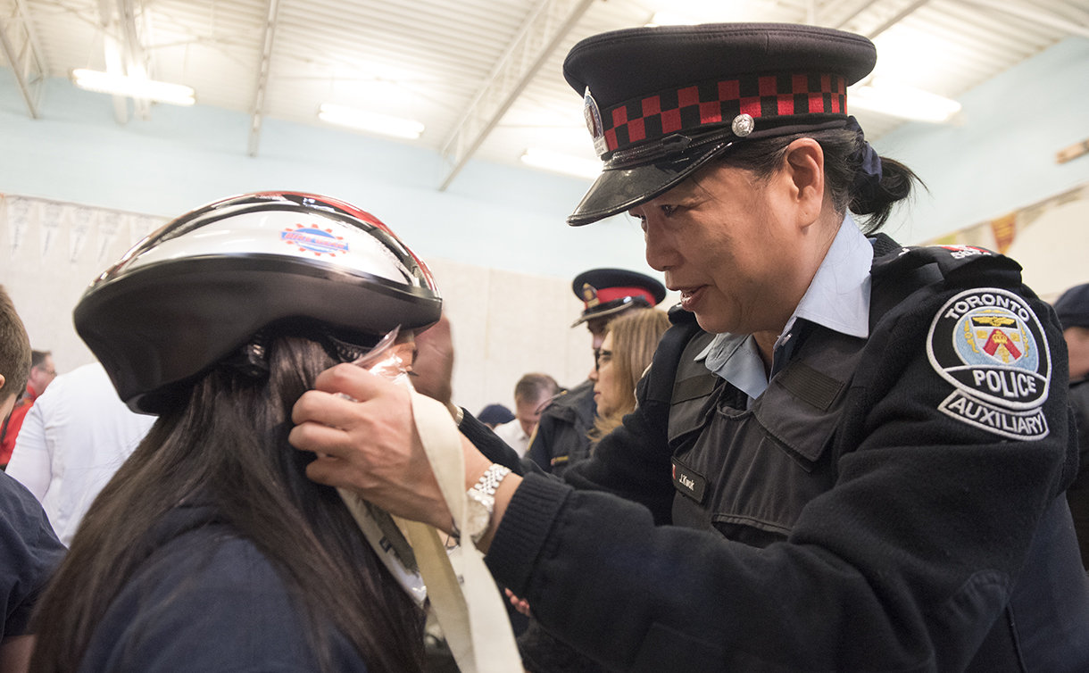 A woman in TPS auxiliary uniforms holds a helmet on a girl's head