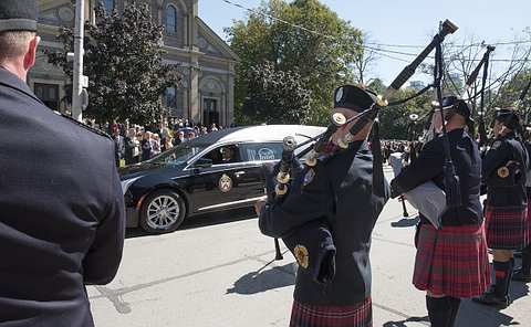 Men in TPS uniform with bagpipes, a hearse driving by