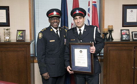 Two men in police uniforms; the man on the right is holding a framed award