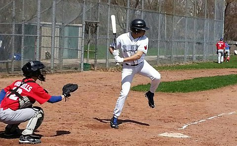 A catcher in position as a batter is ready to swing