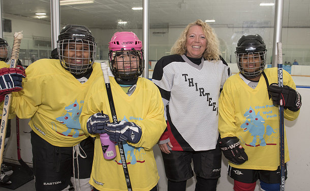 A woman and three girls in hockey uniform