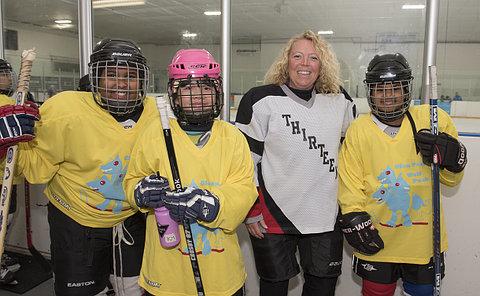 A woman and three girls in hockey uniform