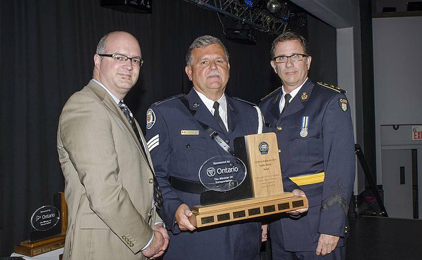 Three men standing in a row, two in police uniform on right, the man in centre holding a trophy