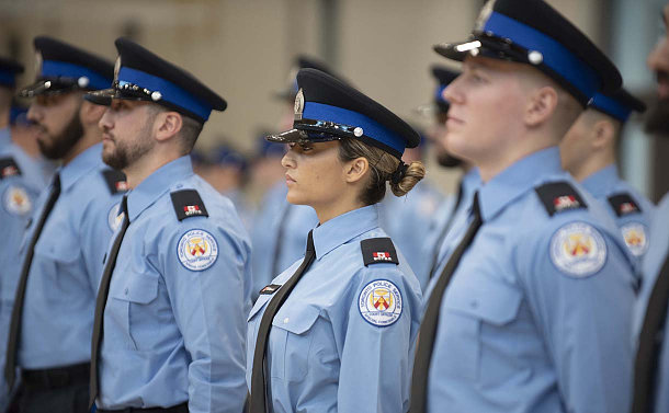 A women in TPS court uniform among a line of other officers