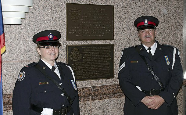 Two police officers standing in front of a wall with two plaques on it